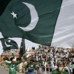 Men wave Pakistan's national flag at a ceremony to mark the country's independence day at Wagah border post near Lahore